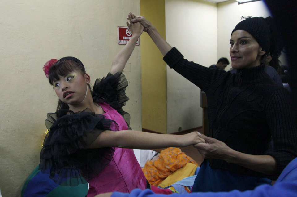 "In this Sept. 21, 2012 photo, a cast member rehearses her dance moves backstage with choreagrapher Luana Choez in preparation for her performance in ""Suenos,"" or �Dreams,� one of Ecuador's most successful musicals, at the Casa de la Cultura theater in Quito, Ecuador. The musical is based in part on the dreams of young people with disabilities and is presented by the nonprofit foundation El Triangulo. (AP Photo/Dolores Ochoa)"