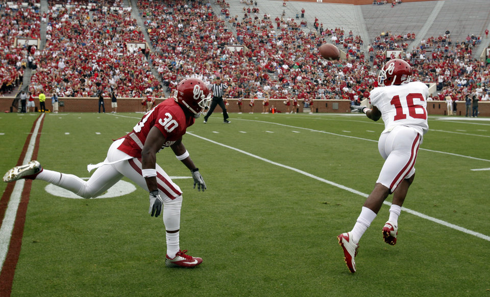 Jaz Reynolds (16) catches a pass and runs for a touchdown in front of Javon Harris (30) during the University of Oklahoma (OU) football team's annual Red and White Game at Gaylord Family/Oklahoma Memorial Stadium on Saturday, April 14, 2012, in Norman, Okla.  Photo by Steve Sisney, The Oklahoman