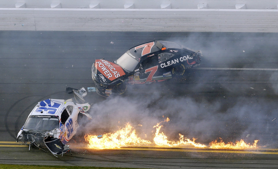 Photo - Kyle Larson's car is on fire as he slides down the track with Regan Smith after being involved in a crash at the conclusion of the NASCAR Nationwide Series auto race Saturday, Feb. 23, 2013, at Daytona International Speedway in Daytona Beach, Fla. Larson's car hit the safety fence sending car parts and other debris flying into the stands injuring spectators. (AP Photo/Chris O'Meara)