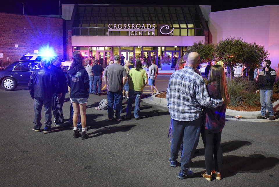 Photo - People stand near the entrance on the north side of Crossroads Center shopping mall in St. Cloud, Minn., Saturday, Sept. 17, 2016. Several people were taken to a hospital with injuries after a stabbing attack at the mall, which ended with the suspected attacker dead inside the mall. (Dave Schwarz/St. Cloud Times via AP)