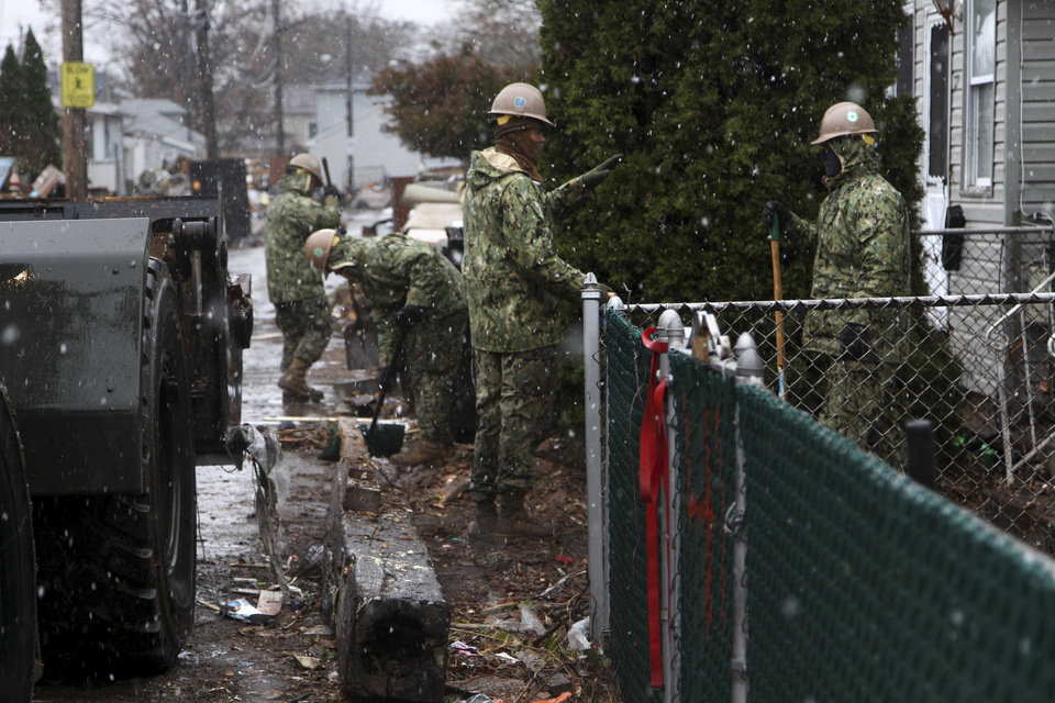 Members of the National Guard clean debris as it snows in the New Dorp section of Staten Island, New York, Wednesday, Nov. 7, 2012.   A Nor'easter is aggravating  already bad conditions in the wake of Superstorm Sandy.  (AP Photo/Seth Wenig) ORG XMIT: NYSW105