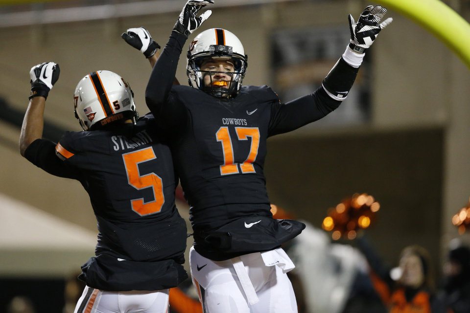 Photo - Oklahoma State wide receiver Charlie Moore (17) celebrates a touchdown against Baylor with teammate Josh Stewart (5) in the second quarter of an NCAA college football game in Stillwater, Okla., Saturday, Nov. 23, 2013. (AP Photo/Sue Ogrocki)