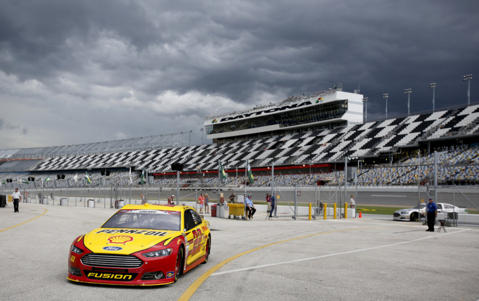 Photo - Joey Logano drives back to the garage as a storm approaches after the first NASCAR Sprint Cup practice session at Daytona International Speedway in Daytona Beach, Fla., Thursday, July 3, 2014. The second practice session was cancelled due to the bad weather. (AP Photo/Terry Renna)