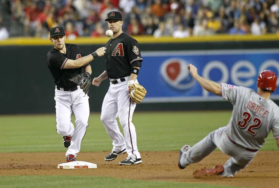 Photo - Arizona Diamondbacks shortstop Chris Owings, left, throws to first to complete a double play after forcing out Cincinnati Reds' Jay Bruce (32) as Diamondbacks' Aaron Hill looks on during the second inning of a baseball game on Saturday, May 31, 2014, in Phoenix. (AP Photo/Ralph Freso)
