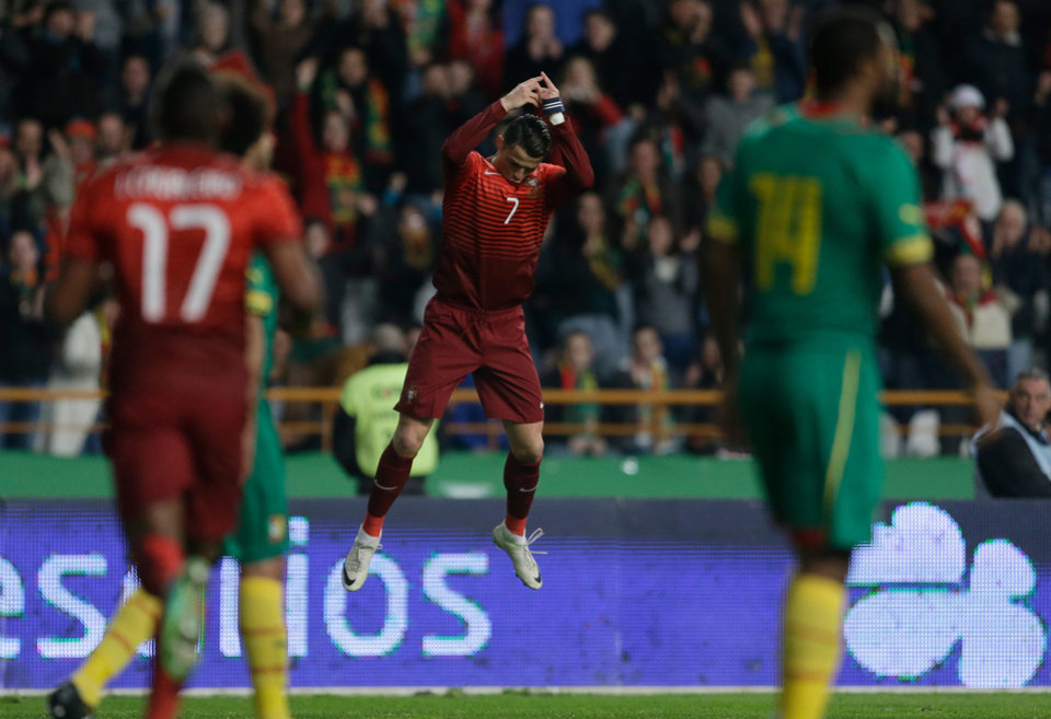 Photo - Portugal's Cristiano Ronaldo, centre, celebrates after scoring the opening goal during their friendly soccer match with Cameroon Wednesday, March 5 2014, in Leiria, Portugal. The game is part of both teams' preparation for the World Cup in Brazil. (AP Photo/Armando Franca)
