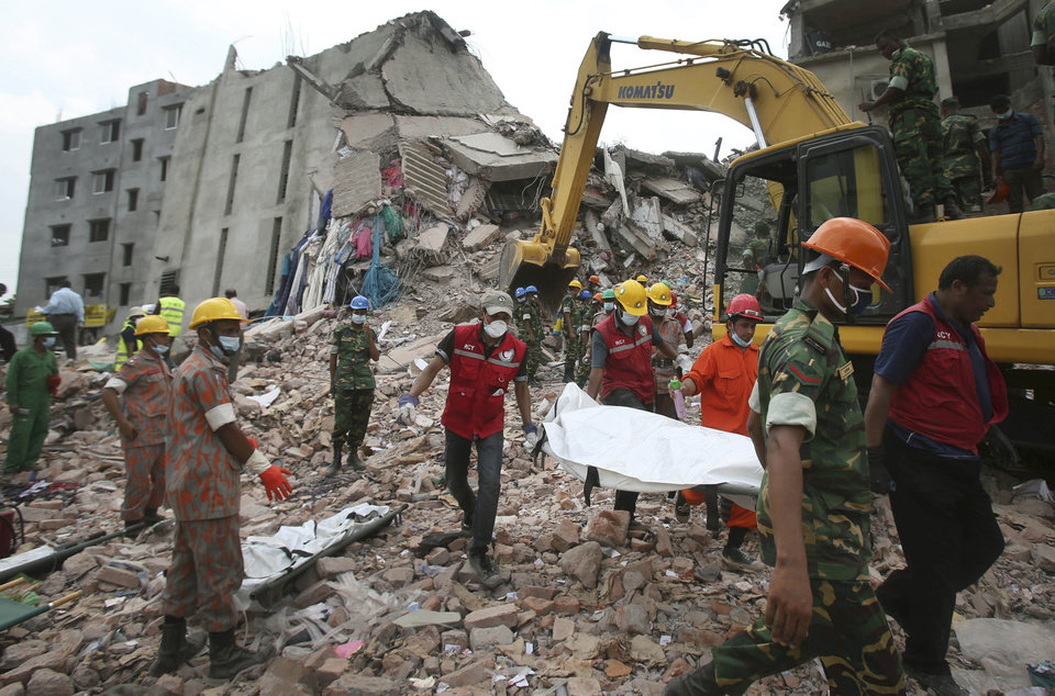 Photo - Workers carry a body that was trapped for almost a week in a  collapsed garment factory building on Tuesday, April 30, 2013 in Savar, near Dhaka, Bangladesh. Emergency workers hauling large concrete slabs from the collapsed eight-story building said Tuesday they expect to find many dead bodies when they reach the ground floor. (AP Photo/Wong Maye-E)