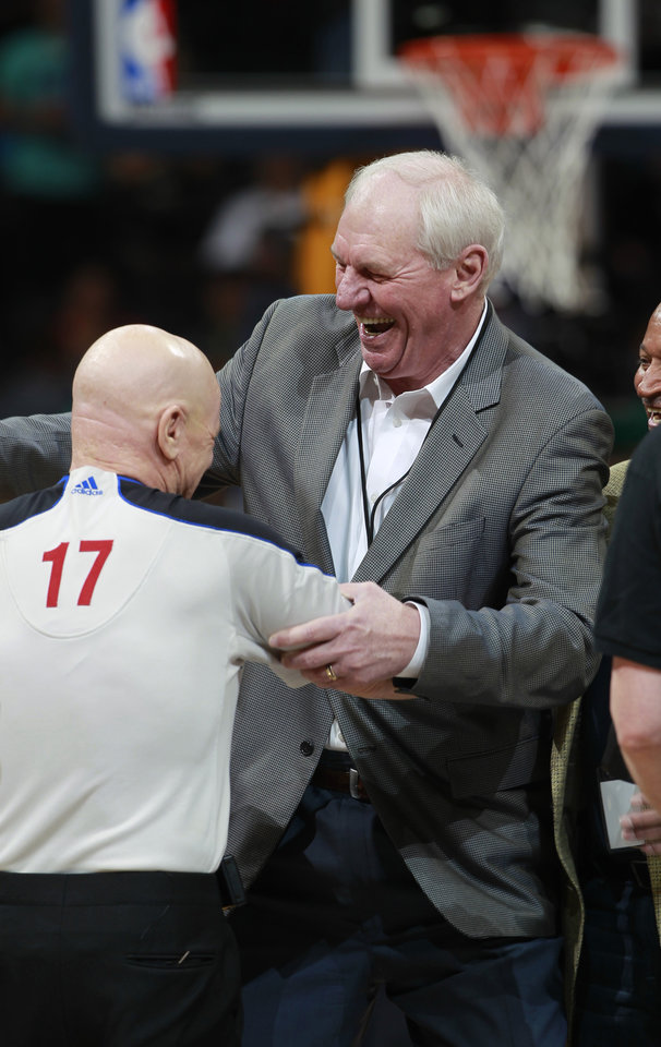 Photo - During part of a pre-game ceremony, former Denver Nuggets head coach and player Dan Issel, right, hands the game ball to referee Joey Crawford for tip off as the Nuggets host the Los Angeles Clippers in the first quarter of an NBA basketball game in Denver on Monday, March 17, 2014. Issel was coach of the Nuggets when they defeated Seattle in the opening round of the NBA Playoffs in 1994 to become the first team seeded as eighth in a conference to defeat the top seed. The Nuggets hornored the 1994 team by wearing the uniform from that season to play the Clippers. (AP Photo/David Zalubowski)