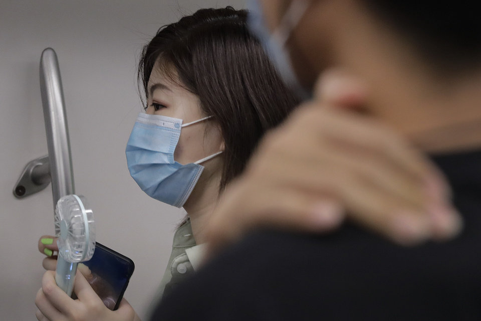 Photo -  A woman wearing a face mask to protect against the new coronavirus uses an electric fan to cool herself as she rides in a subway train in Beijing, Wednesday, July 29, 2020. China reported more than 100 new cases of COVID-19 on Wednesday as the country continues to battle an outbreak in Xinjiang. (AP Photo/Andy Wong)