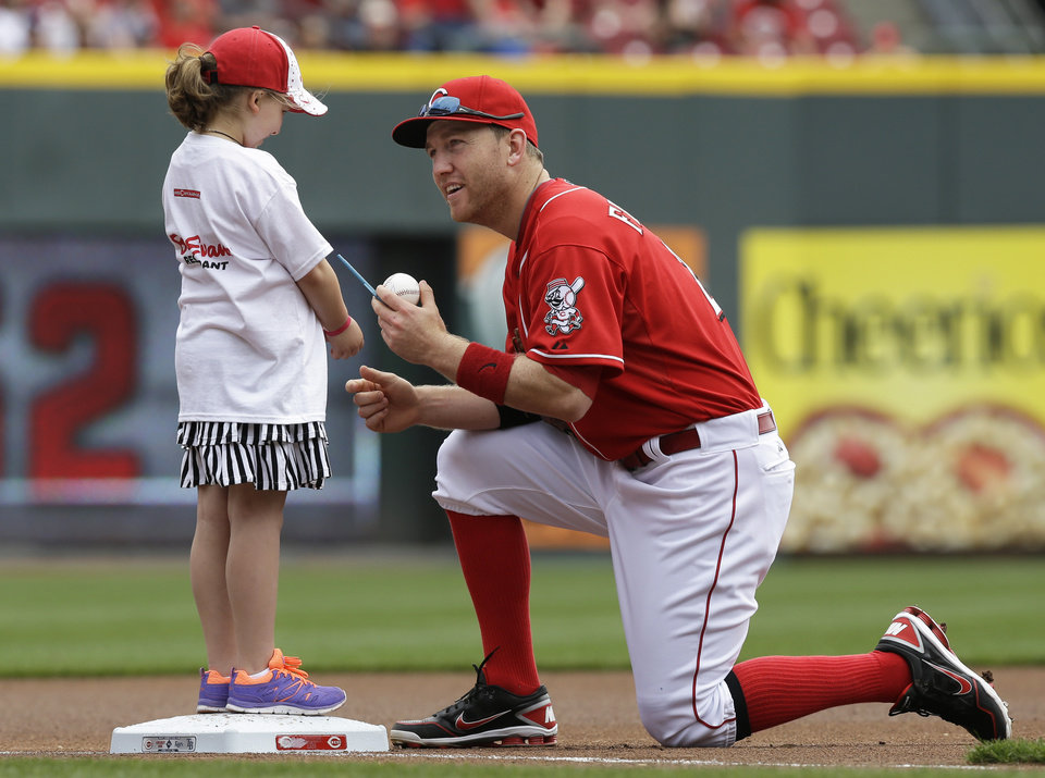 Photo - Cincinnati Reds third baseman Todd Frazier signs an autograph for a young fan before the Reds' baseball game against the Tampa Bay Rays, Sunday, April 13, 2014, in Cincinnati. (AP Photo/Al Behrman)