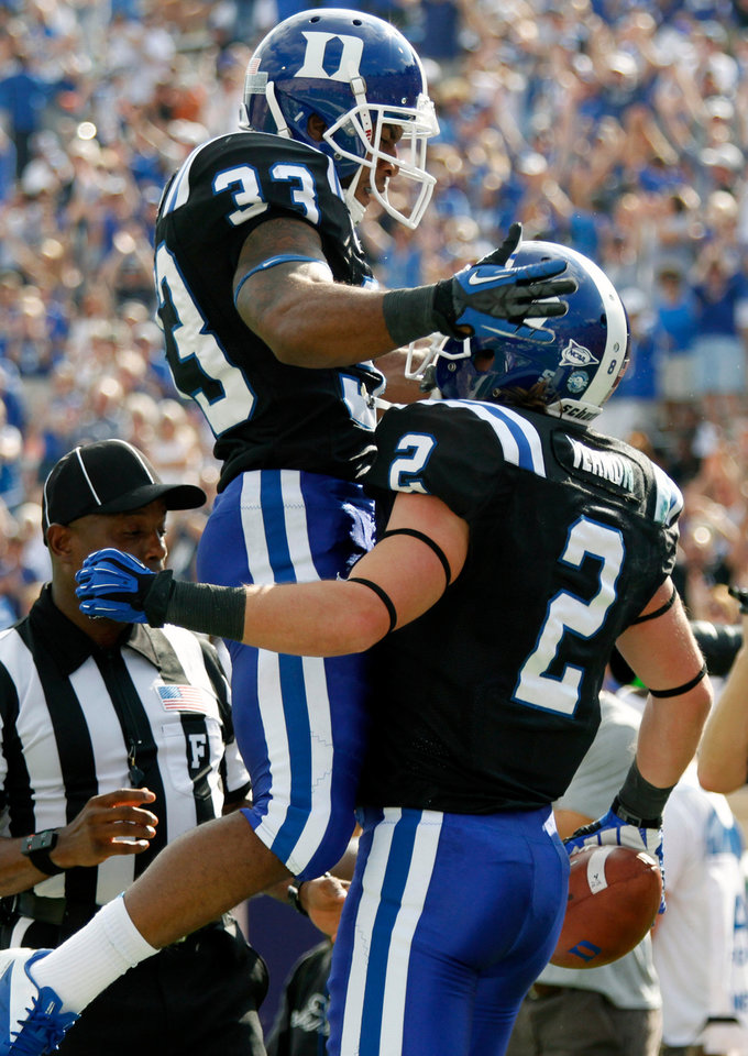 Photo -   Duke wide receiver Conner Vernon (2) gets congratulated by teammate Desmond Scott (33) after he scored a touchdown during the first quarter of an ACC college football game against of Virginia in Durham N.C., on Saturday, Oct. 6, 2012. (AP Photo/The News & Observer, Chris Seward)