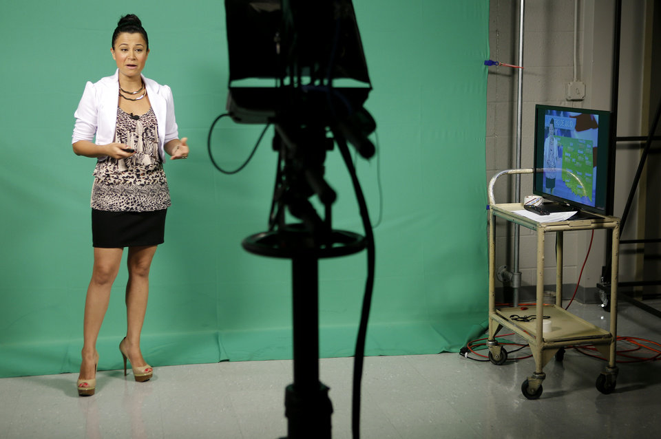 Photo - Jessica Cano does the weather forecast during an Accion Oklahoma newscast on KTUZ-TV, a Telemundo affiliate in Oklahoma City, Wednesday, July 3, 2013. Photo by Bryan Terry, The Oklahoman