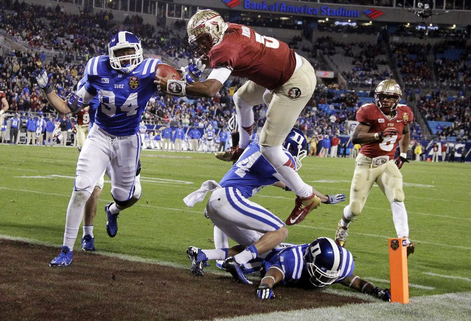 Photo - FILE - In this Dec. 7, 2013, file photo, Florida State's Jameis Winston (5) leaps over Duke's Bryon Fields (14) for a touchdown in the second half of the Atlantic Coast Conference Championship NCAA football game in Charlotte, N.C. Winston has the opportunity to accomplish what only one other player has achieved _ win consecutive Heisman trophies. Twenty-three underclassmen have won the award, but Ohio State running back Archie Griffin was the only one to pull off the feat. (AP Photo/Bob Leverone, File)