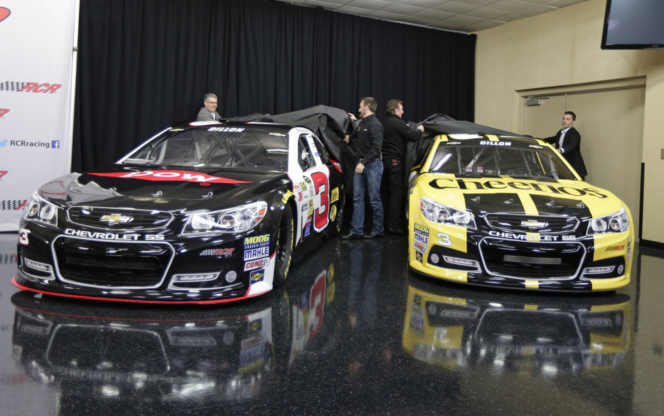 Photo - Austin Dillon, center left, and team owner Richard Childress, center right, help unveil the cars Dillon will drive in the 2014 NASCAR Sprint Cup series during a news conference at Charlotte Motor Speedway in Concord, N.C., Wednesday, Dec. 11, 2013. The late Dale Earnhardt's famed No. 3 will be back on track in the elite Sprint Cup Series next season with Dillon using the number. (AP Photo/Chuck Burton)