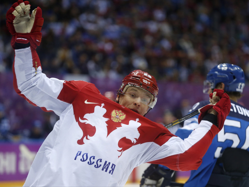 Photo - Russia forward Alexander Syomin loses his balance against Finland in the third period of a men's quarterfinal ice hockey game at the 2014 Winter Olympics, Wednesday, Feb. 19, 2014, in Sochi, Russia. (AP Photo/Julio Cortez)