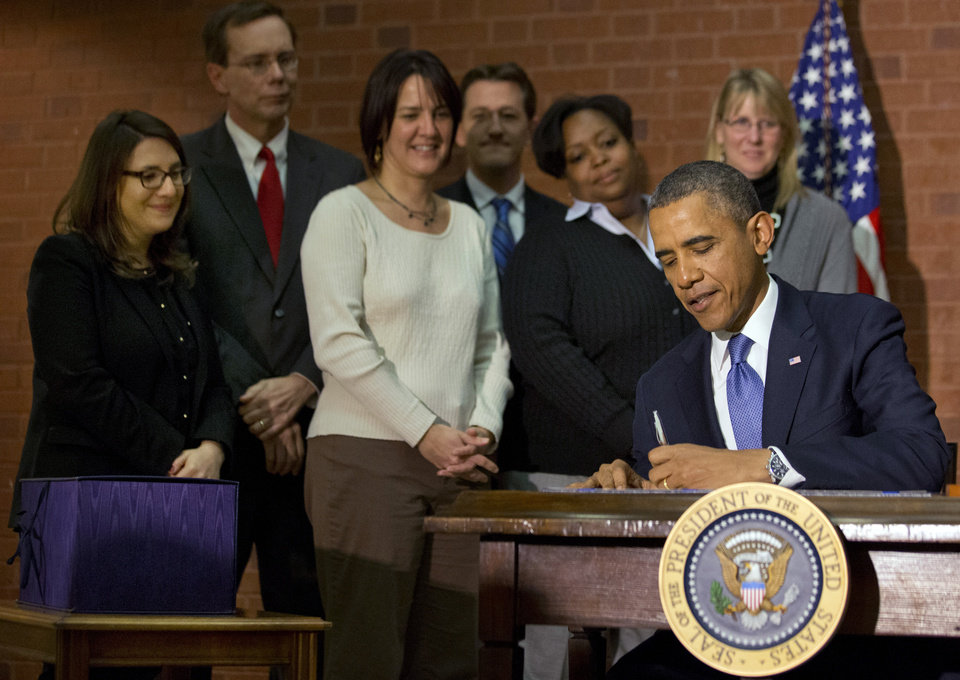 Photo - President Barack Obama signs the $1.1 trillion spending bill that funds the federal government through the end of September, in Washington, Friday, Jan. 17, 2014 at Jackson Place, a conference center near the White House. Obama signed the measure the day before federal funding was set to run out and was joined by aides who did much of the work negotiating it. (AP Photo/Jacquelyn Martin)