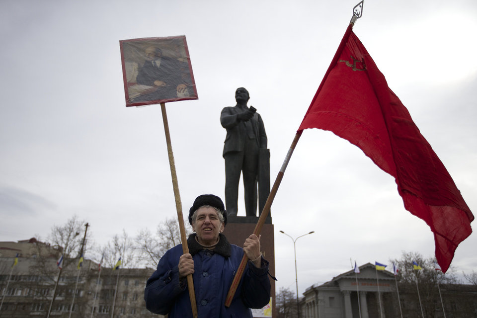 Photo - A local Communist party supporter holds Soviet flag and portrait of Soviet founder Vladimir Lenin as he stands next to Lenin's statue at a square in downtown Simferopol, Ukraine, on Sunday, March 2, 2014. A convoy of hundreds of Russian troops headed toward  Simferopol the regional capital of Ukraine's Crimea region on Sunday, a day after Russia's forces took over the strategic Black Sea peninsula without firing a shot. (AP Photo/Ivan Sekretarev)