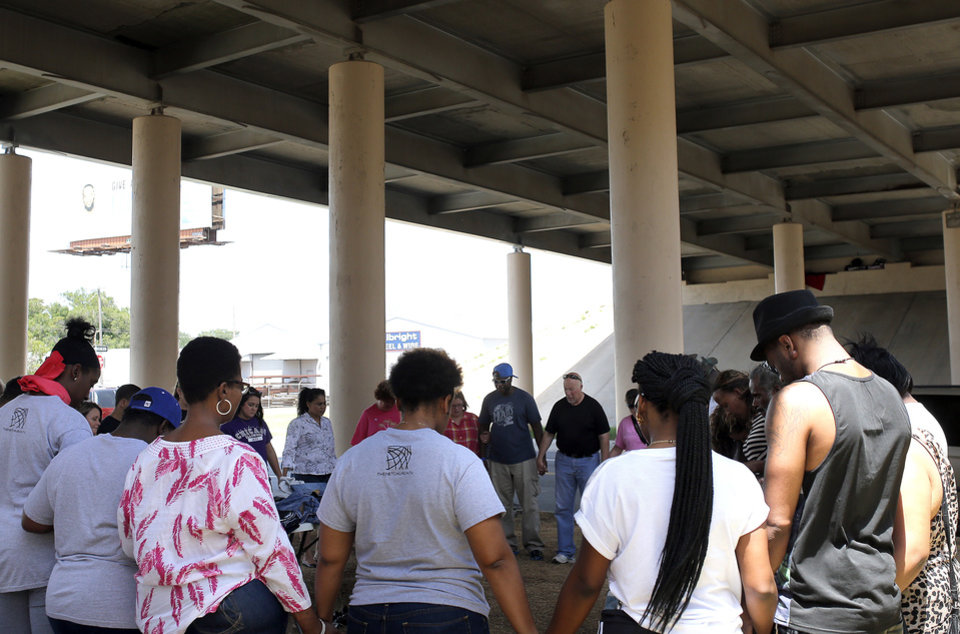 Photo - People pray during a Church Under the Bridge service at an Interstate 40 bridge over Virginia Avenue, between Reno and Lindley avenues in Oklahoma City. Photo by Sarah Phipps, The Oklahoman  SARAH PHIPPS