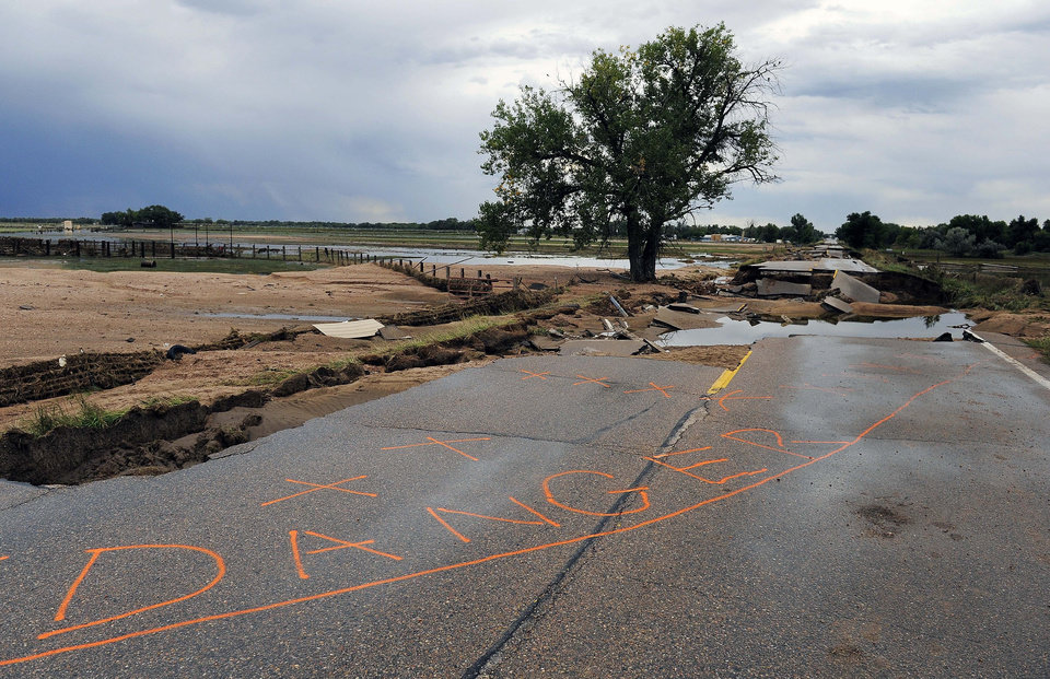 Photo - Danger is spray-painted on a damaged section of Old Highway 34 in Loveland, Colo., on Wednesday, Sept. 18, 2013. As floodwaters recede, cleanup and damage assessment continues after historic flooding. (AP Photo/Chris Schneider)