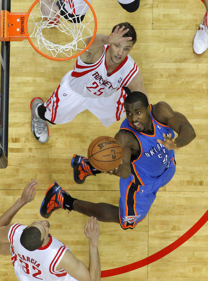 Photo - Oklahoma City's Serge Ibaka (9) goes to the basket between Houston's Francisco Garcia (32), and Chandler Parsons (25) during Game 3 in the first round of the NBA playoffs between the Oklahoma City Thunder and the Houston Rockets at the Toyota Center in Houston, Texas, Sat., April 27, 2013. Oklahoma City won 104-101. Photo by Bryan Terry, The Oklahoman
