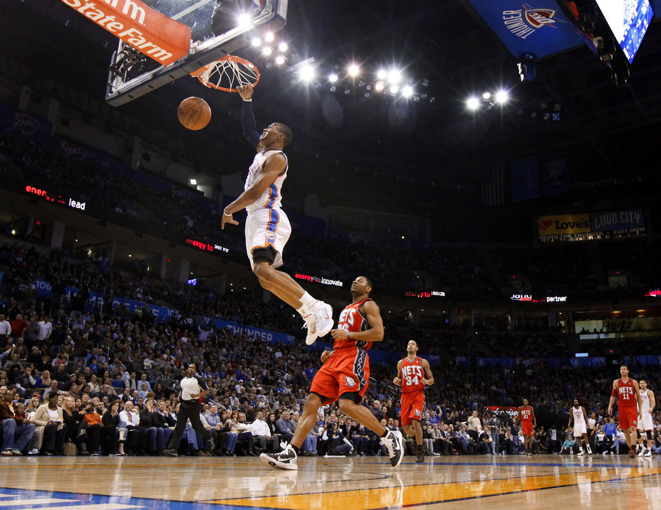 Photo - Oklahoma City's Russell Westbrook dunks the ball in front of New Jersey's Stephen Graham during the NBA basketball game between the Oklahoma City Thunder and the New Jersey Nets at the Oklahoma City Arena, Wednesday, Dec. 29, 2010.  Photo by Bryan Terry, The Oklahoman ORG XMIT: KOD