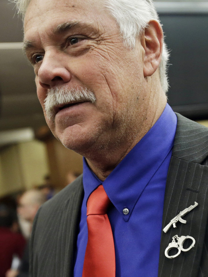 Photo - Gun rights advocate Rep. Tony Cornish, R-Good Thunder, wears miniature assault-type rifle and handcuffs on his suit coat as he talks with reporters during a break in a Minnesota house public safety committee hearing on two bills dealing with the gun violence issue at the State Capitol Tuesday, Feb. 5, 2013 in St. Paul, Minn. (AP Photo/Jim Mone)