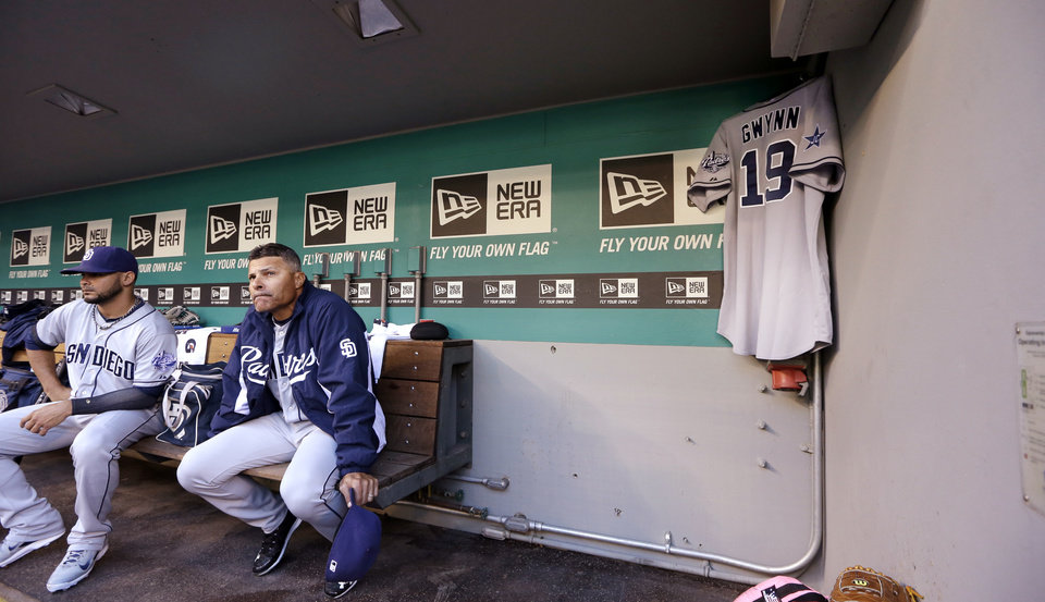 Photo - San Diego Padres' Alex Torres, left, and coach Jose Valentine sit near a jersey hanging in the team's dugout honoring Tony Gwynn before a baseball game against the Seattle Mariners Monday, June 16, 2014, in Seattle. It was announced earlier Monday that Gwynn, who had more than 3,100 hits during a career spanning two decades, died at age 54 following a battle with oral cancer. (AP Photo/Elaine Thompson)