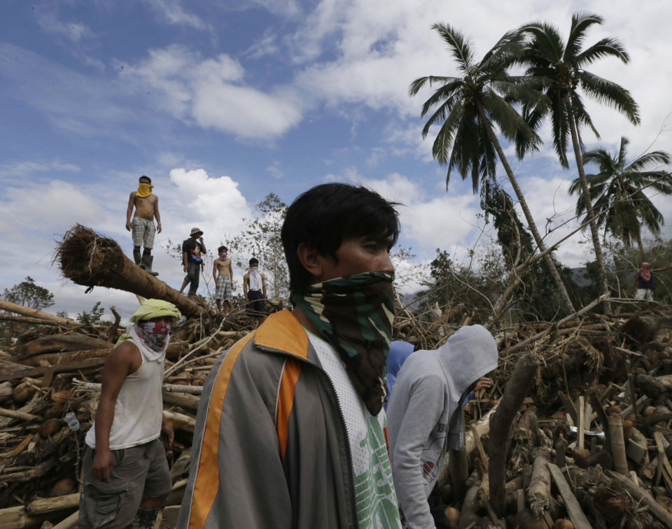Photo - Relatives continue to search for their missing kin following a flash flood brought by Tuesday's Typhoon Bopha at New Bataan township, Compostela Valley in southern Philippines Friday Dec. 7, 2012. Rescuers were digging through mud and debris Friday to retrieve more bodies strewn across a farming valley in the southern Philippines by a powerful typhoon. (AP Photo/Bullit Marquez)