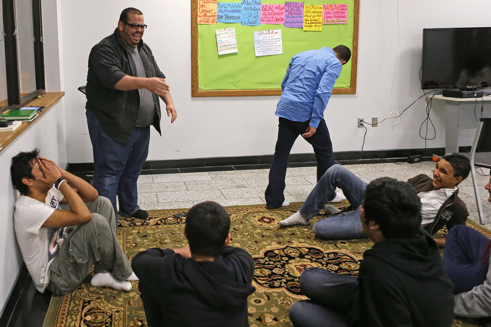 Photo - The Islamic Society of Greater Oklahoma's new youth director Abdur-Rahman Taleb laughs as he demonstrates an Islamic principle as part of recent youth activities at the Mercy School complex, 14001 N Harvey.   BRYAN TERRY - THE OKLAHOMAN