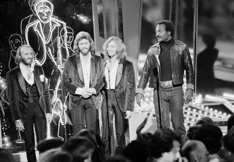 Photo -   FILE - In this Dec. 8, 1977, file photo, The Bee Gees, from left, Maurice, Barry and Robin Gibb, join actor Jim Brown, right, on Stage 14 of Paramount Studios during a disco party for the premiere of