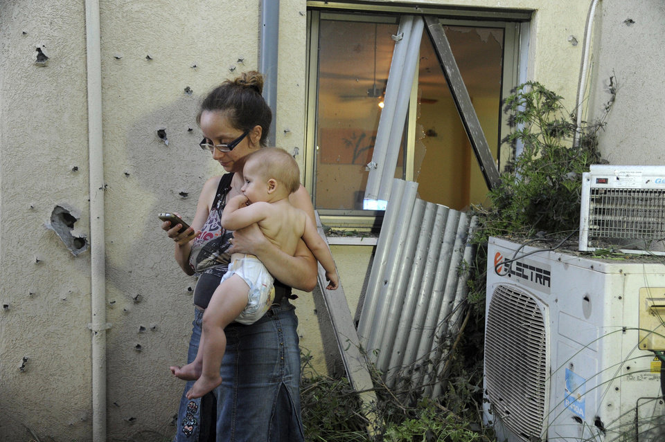 Photo - An Israeli woman holds her child outside her home damaged by a rocket fired from Lebanon in Shavei Tzion outside Nahariya in northern Israel, Thursday, Aug. 22, 2013. Military spokesman Lt. Col. Peter Lerner said Thursday that three rockets landed in northern Israel, while one was shot down. (AP Photo/Jinipix) ISRAEL OUT