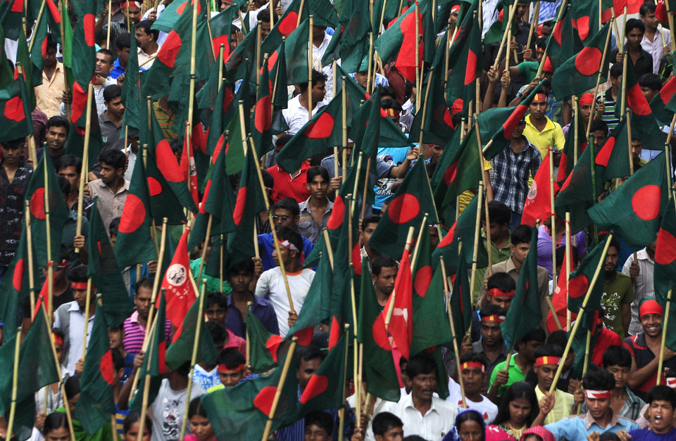 Photo - Protesters carry the national flags and shout slogans during a May Day rally on Wednesday May 1, 2013 in Dhaka, Bangladesh. Thousands of workers paraded through central Dhaka on May Day to demand safer working conditions and the death penalty for the owner of a building housing garment factories that collapsed last week in the country's worst industrial disaster, killing at least 402 people and injuring 2,500. (AP Photo/Ismail Ferdous)