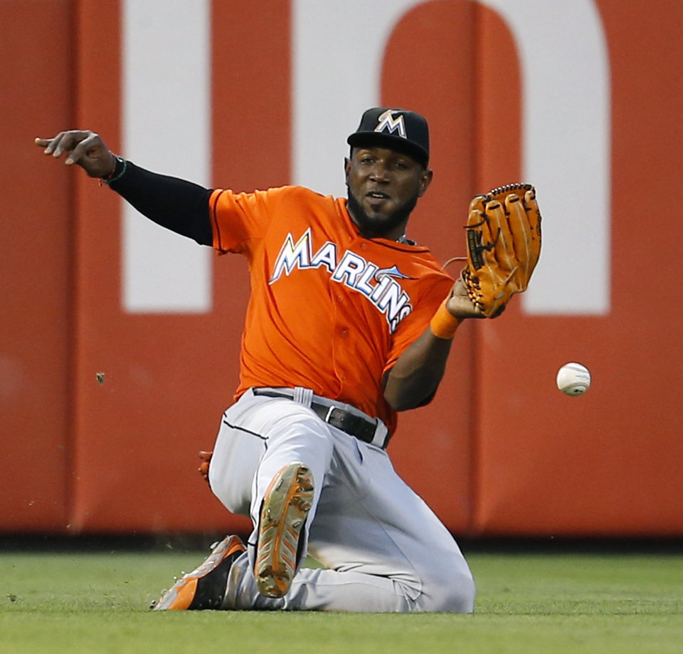 Photo - Miami Marlins left fielder Marcell Ozuna cannot catch a single by Philadelphia Phillies' Marlon Byrd during the fourth inning of a baseball game, Wednesday, June 25, 2014, in Philadelphia. (AP Photo/Matt Slocum)