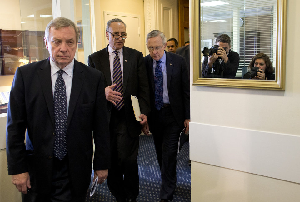 Photo - Sen. Dick Durbin, D-Ill., left, Sen. Chuck Schumer, D-N.Y., center, and Senate Majority Leader Sen. Harry Reid, D-Nev., arrive for a news conference on Capitol Hill on Saturday, Oct. 12, 2013 in Washington. The federal government remains partially shut down and faces a first-ever default between Oct. 17 and the end of the month. (AP Photo/ Evan Vucci)  ORG XMIT: DCEV116
