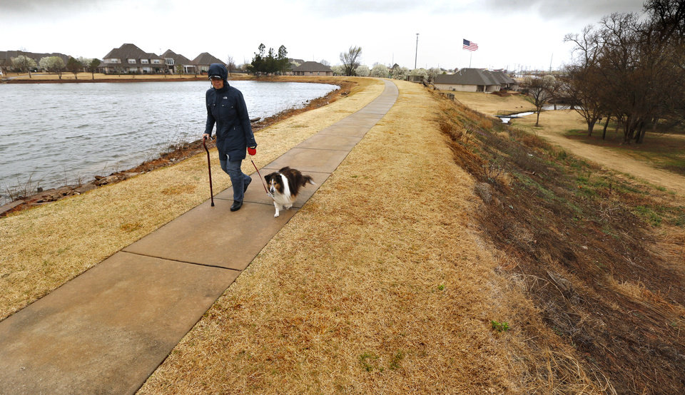 Photo -  Summit Lakes resident Pat Culbert walks her dog on a paved walkway across a dam that is causing problems for the addition's property owners. [PHOTO BY STEVE SISNEY, THE OKLAHOMAN]