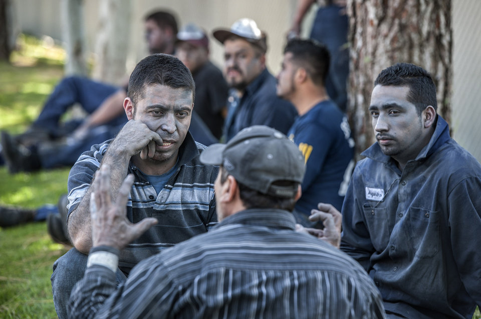 Photo - Workers from a chrome finishing company sit outside talking after an explosion in La Habra, Calif., Tuesday, April 29, 2014. Authorities say eight people have been hurt, three critically, in an explosion and fire at a commercial building in south Los Angeles County. (AP Photo/The Orange County Register, Bruce Chambers)