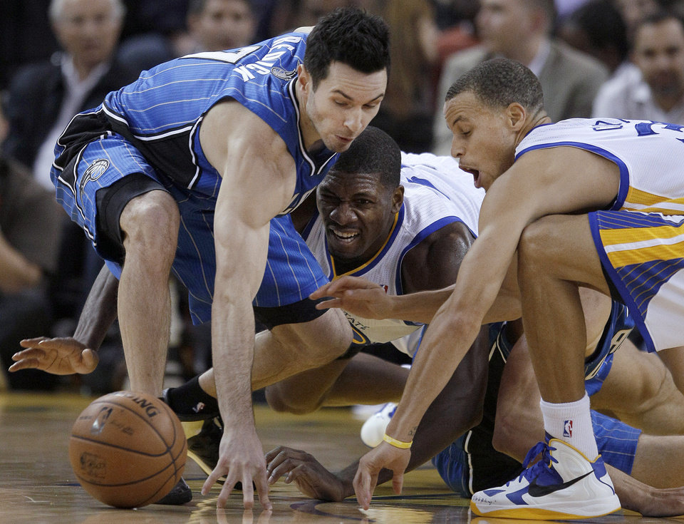 Orlando Magic guard J.J. Redick, left, reaches for a loose ball next to Golden State Warriors center Festus Ezeli, center, and guard Stephen Curry during the first quarter of an NBA basketball game in Oakland, Calif., Monday, Dec. 3, 2012. (AP Photo/Jeff Chiu)