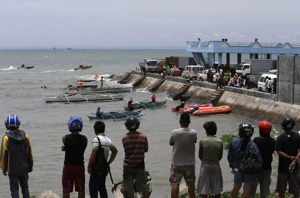 Photo - A crowd watches as divers continue their search and rescue operation off Talisay coast, Cebu province Sunday, Aug. 18, 2013 following Friday night's collision of the passenger ferry MV Thomas Aquinas and the cargo ship MV Sulpicio Express Siete in central Philippines. Divers plucked two more bodies from the sunken passenger ferry on Sunday and scrambled to plug an oil leak in the wreckage after a collision with a cargo ship. The accident near the central Philippine port of Cebu that has left 34 dead and more than 80 others missing. (AP Photo/Bullit Marquez)