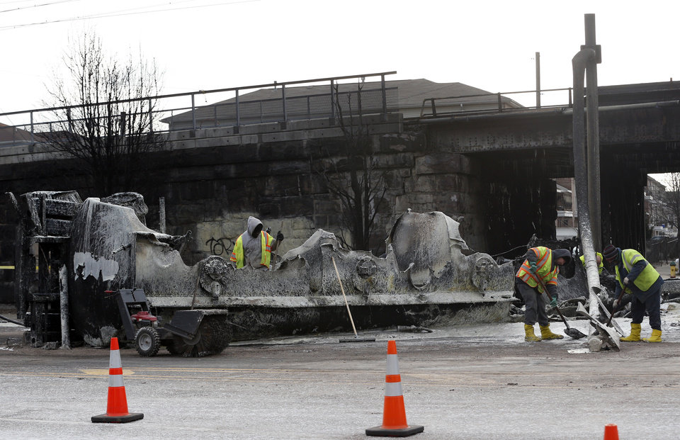 Photo - Crews clean up the site where a tanker overturned and burst into flames early in the morning near train tracks on Route 21 in Newark, N.J., Thursday, March 13, 2014.  The tanker burst into flames after colliding with a car on McCarter Highway adjacent to Amtrak's Northeast Corridor rail line in Newark at about 1:45 a.m. Thursday. That caused problems for Amtrak's signals and overhead wires. Amtrak service is running with minor delays. (AP Photo/Julio Cortez)
