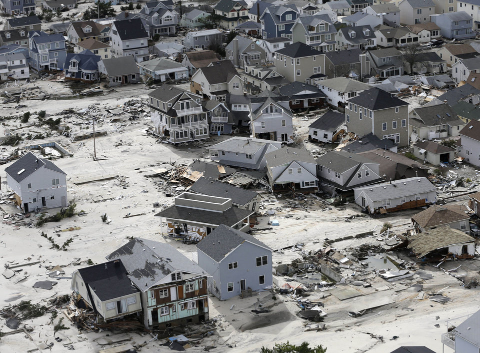 Photo - FILE - This Oct. 31, 2012 file photo shows the destroyed homes left in the wake of superstorm Sandy in Seaside Heights, N.J. Superstorm Sandy may have one more nasty surprise still to come: higher taxes. Unless shore towns from Rhode Island to New Jersey get a big influx of aid from the state and federal governments, which are themselves strapped for cash, they will have no choice but to raise taxes on homes and businesses that survived to make up for the loss.(AP Photo/Mike Groll, file)