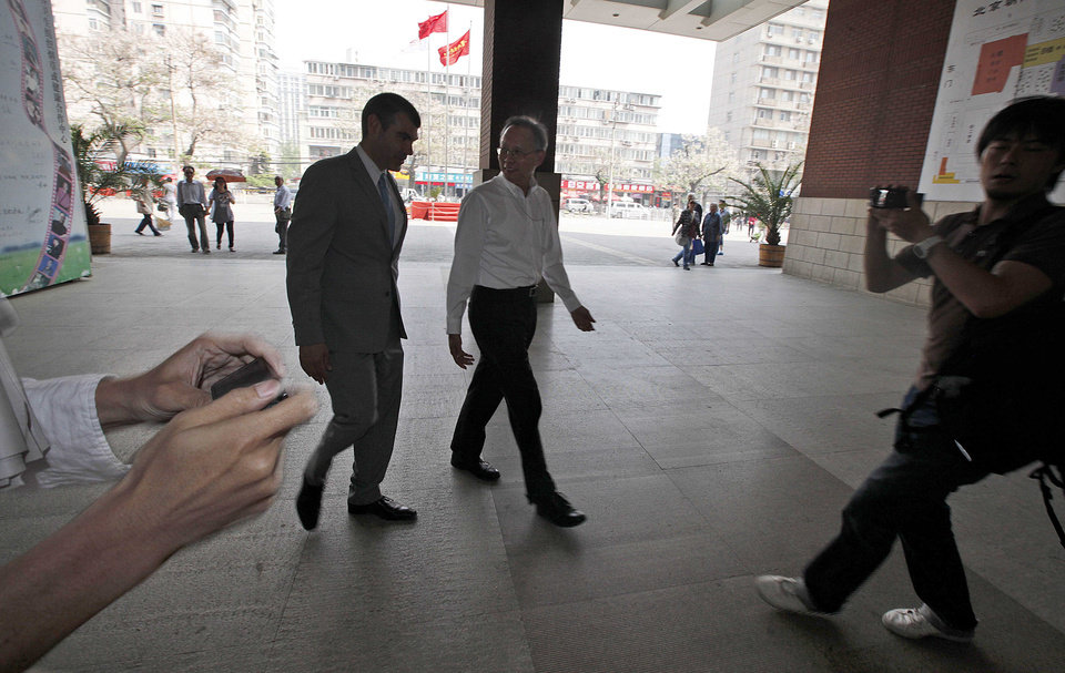 Photo -   Robert S. Wang, center, deputy chief of mission at the U.S. embassy in Beijing, walks with an unidentified U.S. embassy staff, left, outside the hospital where blind activist lawyer Chen Guangcheng is recuperating in Beijing Friday, May 4, 2012. The blind Chinese activist at the center of a diplomatic standoff between the United States and China said Friday his situation is