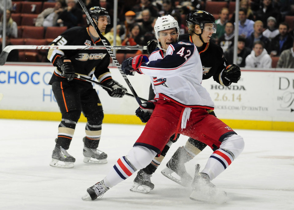 Photo - Anaheim Ducks defenseman Hampus Lindholm, back right, of Sweden, and Columbus Blue Jackets center Artem Anisimov (42), of Russia, fight for the puck during the first period of an NHL hockey game, Monday, Feb. 3, 2014, in Anaheim, Calif. (AP Photo/Gus Ruelas)