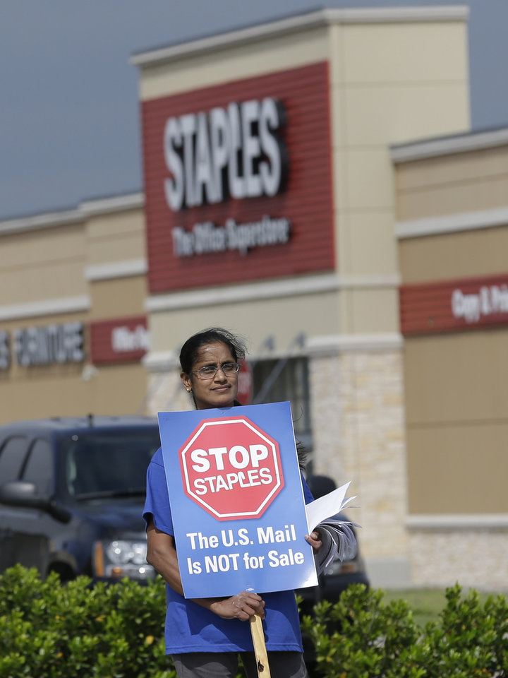 Photo - Postal worker Sophia Joseph holds a sign outside a Staples store during a protest in Dallas, Thursday, April 24, 2014.  Thousands of postal workers around the nation are expected to picket outside Staples' stores to protest a pilot program of postal counters in the stores that are staffed with Staples employees. (AP Photo/LM Otero)
