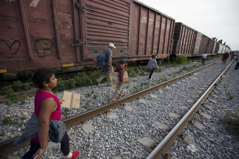 Photo - In this July 12, 2014, photo, migrants walk along the rail tracks after getting off a train during their journey toward the U.S.-Mexico border in Ixtepec, Mexico. The surge in unaccompanied minors and women with children migrating from Central America has put new attention on decades-old smuggling organizations.  (AP Photo/Eduardo Verdugo)