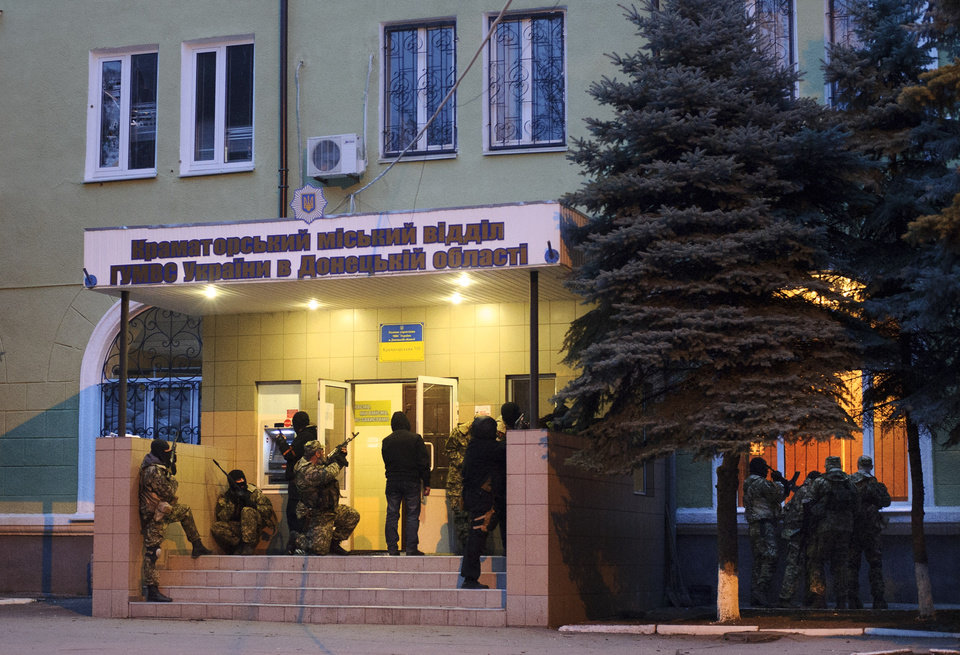 Photo - In this photo taken on Saturday, April  12, 2014, Armed pro-Russian activists occupy the police station in the eastern Ukraine town of Kramatorsk. The interior minister overnight reported an attack on a police in the city of Kramatorsk, close to the city of Slovyansk. A video from local news web-site Kramatorsk.info showed a group of camouflaged men armed with automatic weapons storming the building. The news web-site also reported that supporters of the separatist Donetsk People's Republic have occupied the administration building, built a barricade with tires around it and put a Russian flag nearby.  (AP Photo/Maxim Dondyuk, Russian Reporter magazine) MAGAZINES OUT
