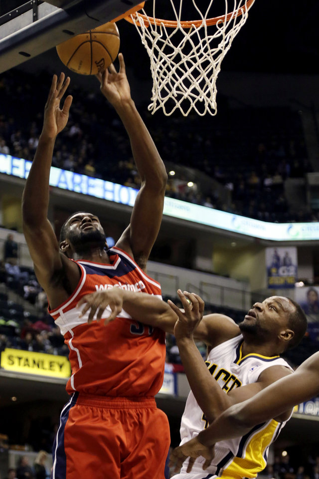 Washington Wizards forward Chris Singleton, left, shoots over Indiana Pacers forward Sam Young during the first half of an NBA basketball game, Wednesday, Jan. 2, 2013, in Indianapolis. (AP Photo/AJ Mast)