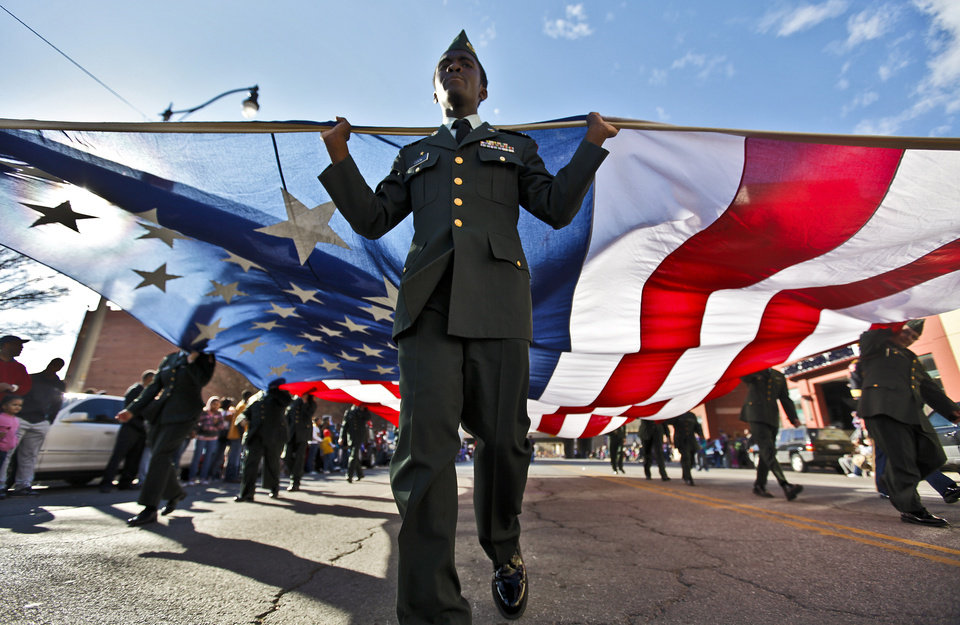 A member of the Northwest Classen ROTC carries the American Flag during Martin Luther King Jr. Day parade through downtown Oklahoma City on Monday, Jan. 16, 2012, in Oklahoma City, Okla. Photo by Chris Landsberger, The Oklahoman