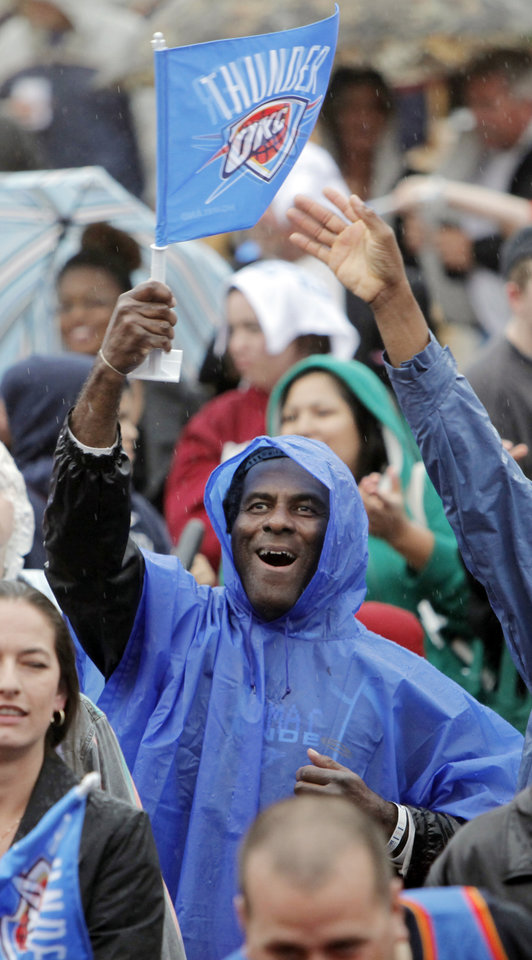 Photo - Fan Larry Fry waves a Thunder flag in the rain during the Thunder FanFest in Bricktown, celebrating the team making it to the NBA playoffs, in Oklahoma City, Friday, April 16, 2010. Photo by Nate Billings, The Oklahoman