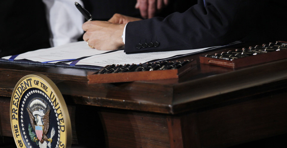 FILE - This March 23, 2010 file photo shows Ttwenty two pens next to President Barack Obama as he signs the health care reform bill in the East Room of the White House in Washington. Your medical plan is  facing an unexpected expense, so you probably are, too. It's a new, $63-per-head fee to cushion the cost of covering people with pre-existing conditions under President Barack Obama�s health overhaul. The charge, buried in a recent regulation, works out to tens of millions of dollars for the largest company health plans, and much of that is likely to be passed on to employees. Multiple pens are used to sign legislation, and then distributed to supporters of the legislation. (AP Photo/Charles Dharapak, File)