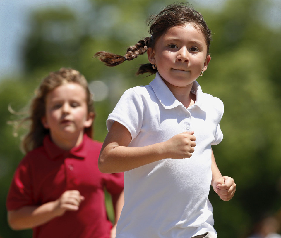 Photo - First graders Stephanie Gibbs, right, and Maggie Calvo run on the school track at Monroe Elementary as part of their participation in this year's Kid's Marathon.  More than 120 students from Monroe Elementary School in Oklahoma City will finish the final 1.2 miles of the Kid's Marathon during the Oklahoma City Memorial Marathon on Sunday. Tuesday,  April  24, 2012.        Photo by Jim Beckel, The Oklahoman