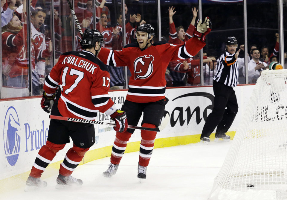 New Jersey Devils defenseman Mark Fayne celebrates a goal by Ilya Kovalchuk (17), of Russia, during the second period of an NHL hockey game against the Tampa Bay Lightning, Thursday, Feb. 7, 2013, in Newark, N.J. (AP Photo/Julio Cortez)